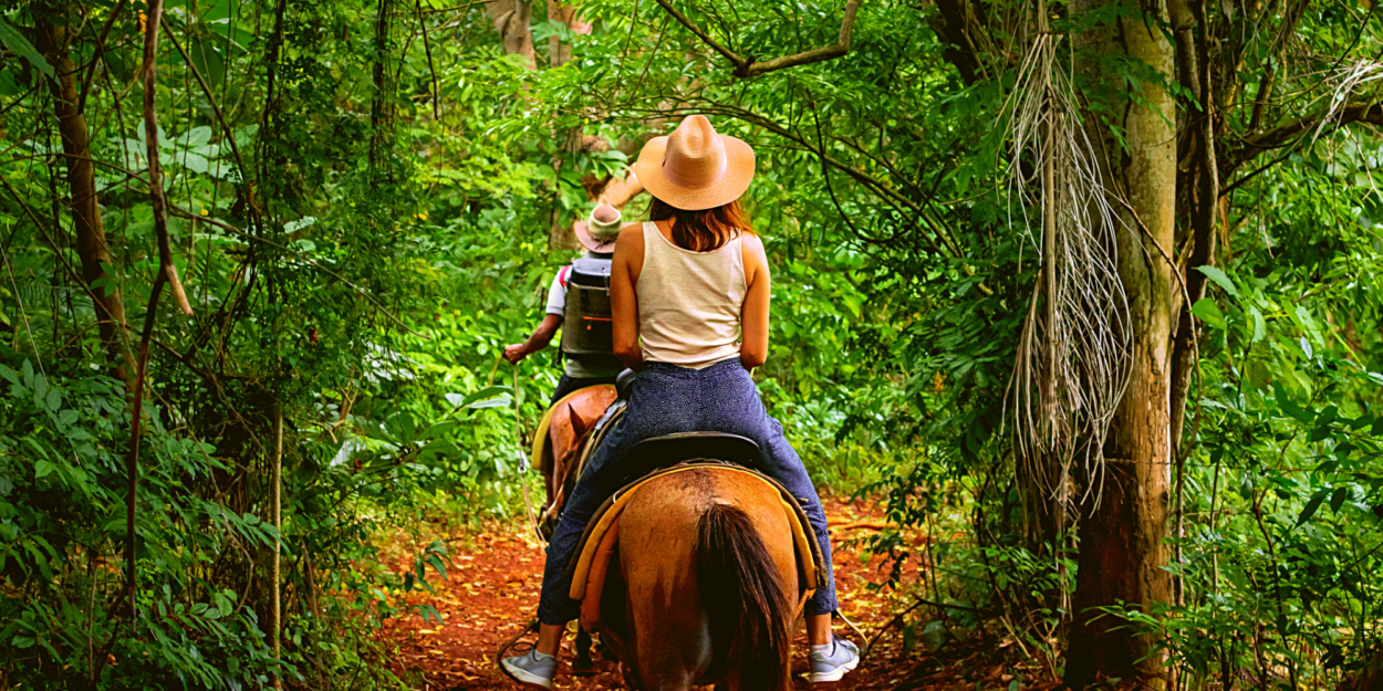A family riding on horses through the forest in Costa Rica