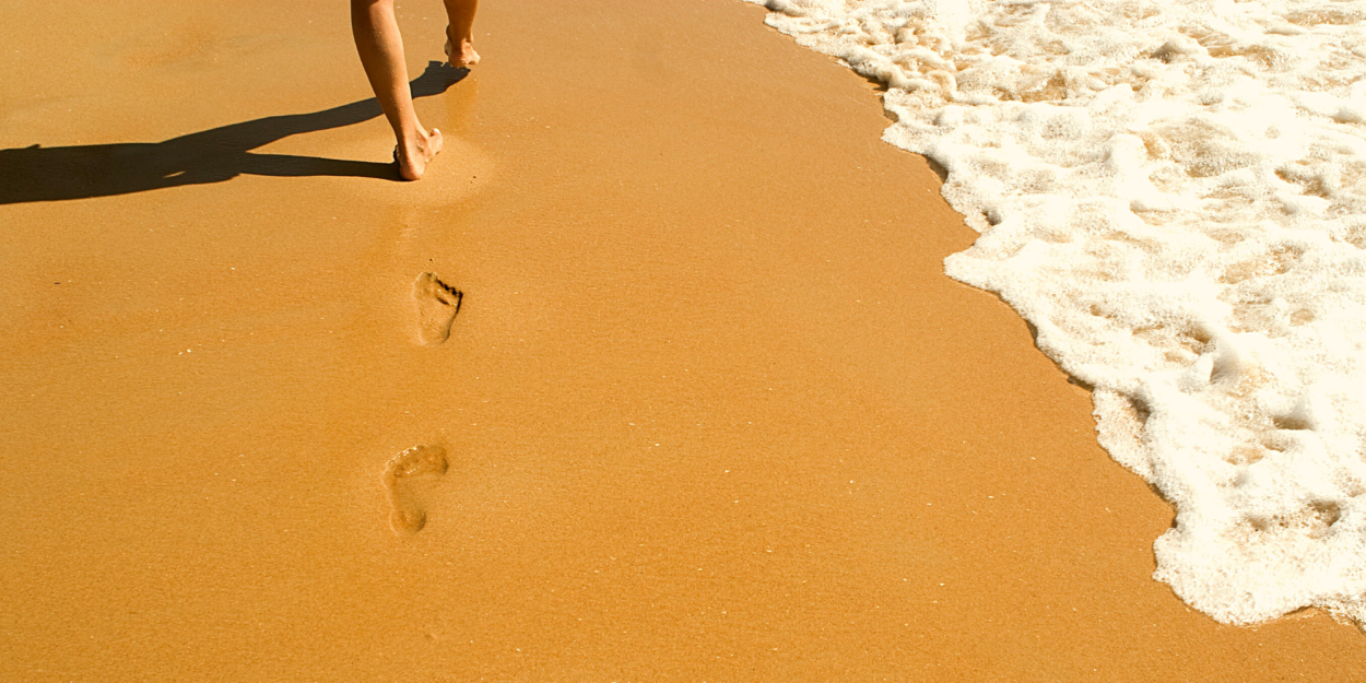 One person walks alone along a beach, leaving footprints in the sand