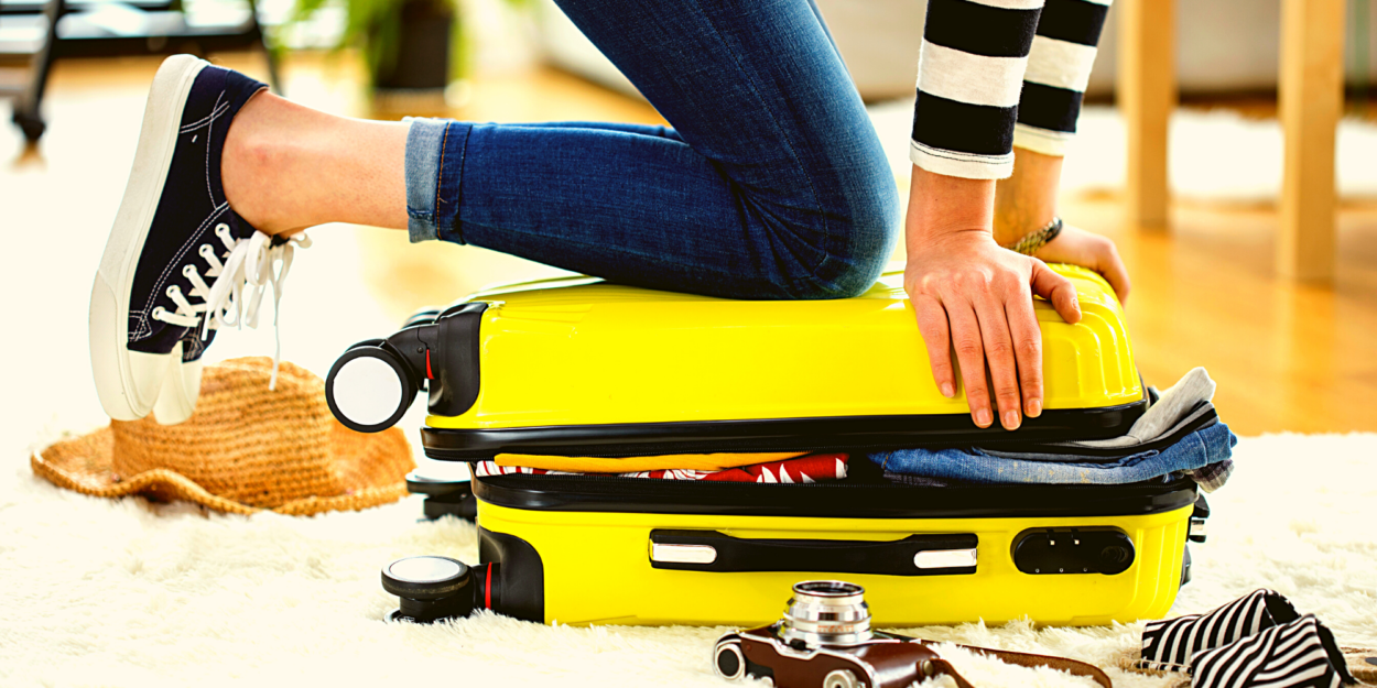 An overstuffed yellow suitcase