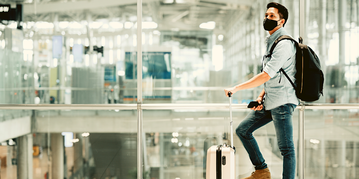 A man in a mask standing with his suitcase at an airport