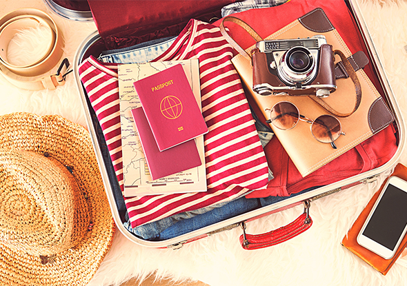 An open suitcase with passports, camera, and clothes