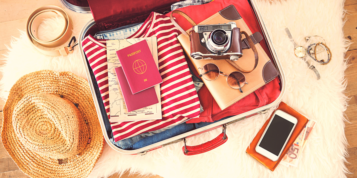 A camera and phone on top of a packed suitcase
