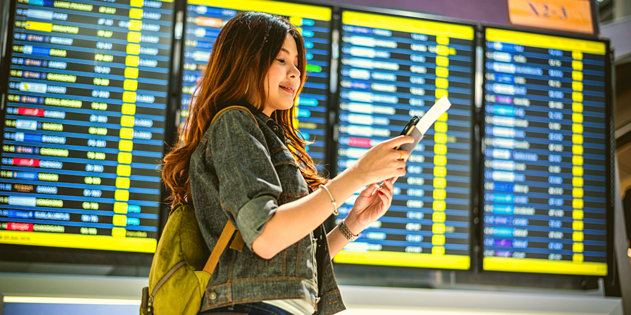 A woman checks her phone in front of an airport reader board