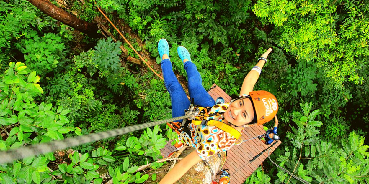 A woman rappelling on a zipline course