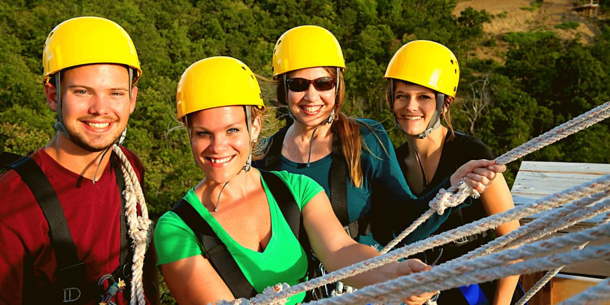 Four friends at a zipline platform.