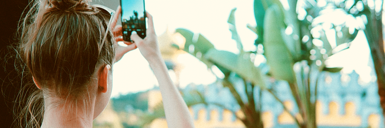 A girl taking pictures with her phone of some banana trees