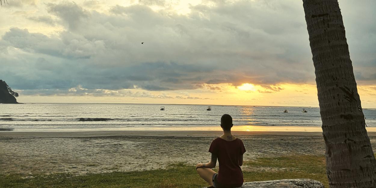 Woman sitting, watching the sunset on Samara Beach in Costa Rica