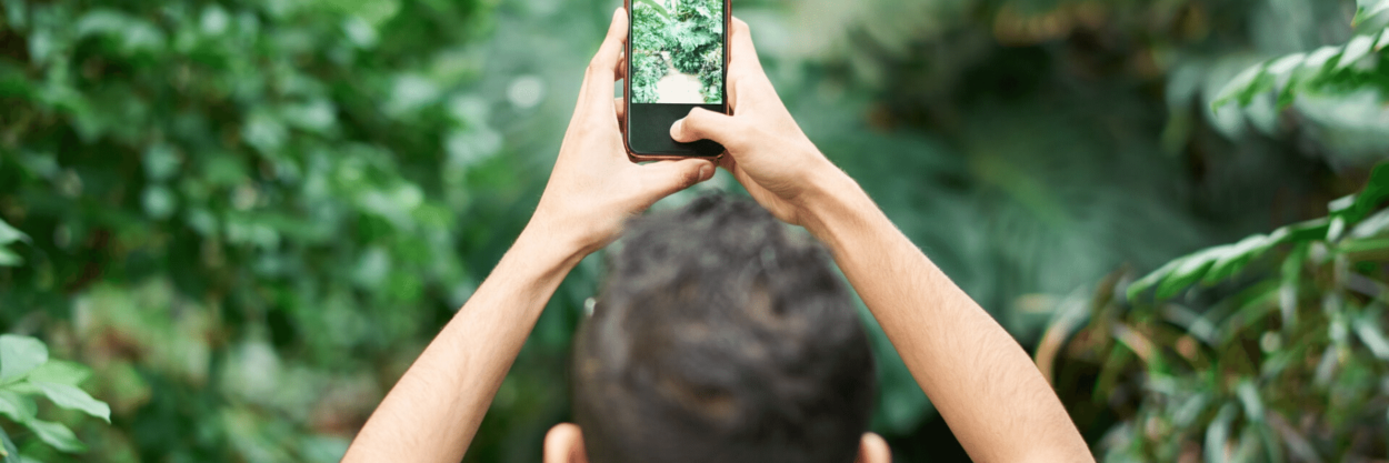 A man taking a picture over his head