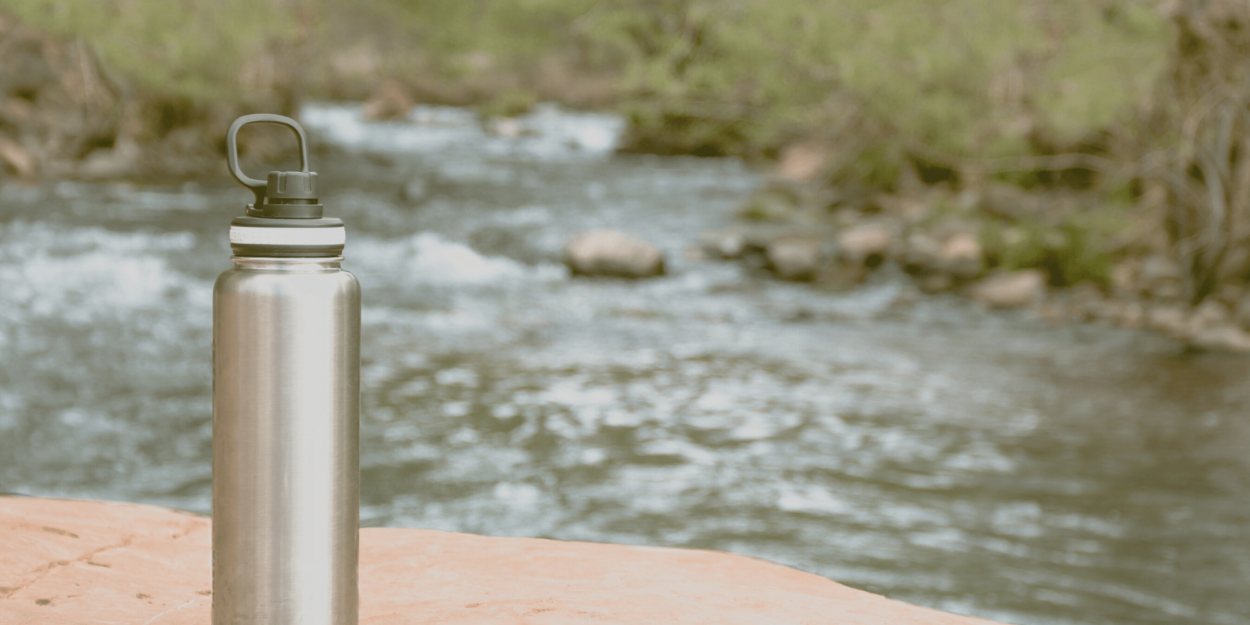 A metal water bottle on the side of a river in a Costa Rican national park