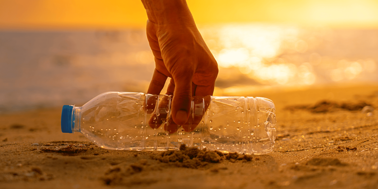 Person picking up a plastic bottle on the beach
